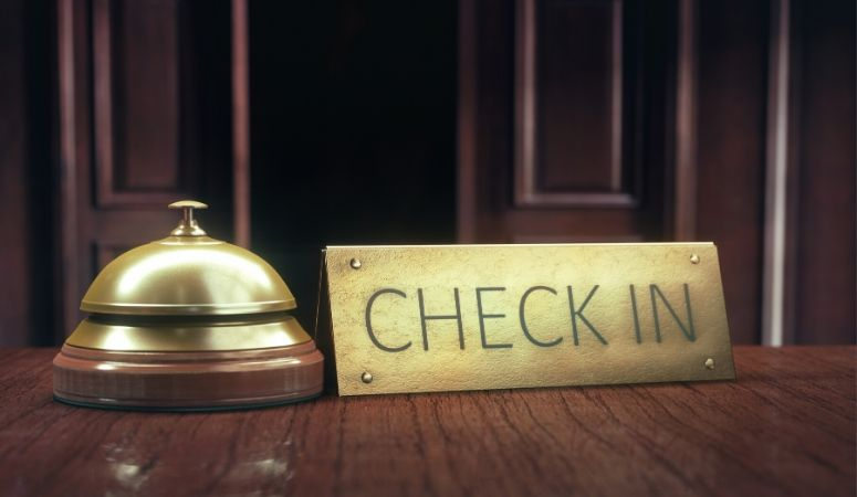 Hotel check in desk with bell and check in sign