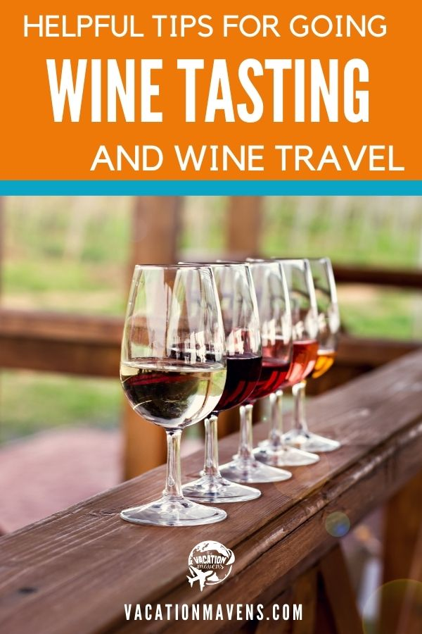 Helpful tips for going wine tasting and wine travel with five wine glasses lined up on a railing and vineyards in the background